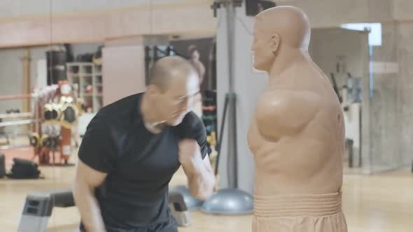 Persistent Caucasian Sportsman Training with Mannequin in Sports Club. Side View Portrait of Adult