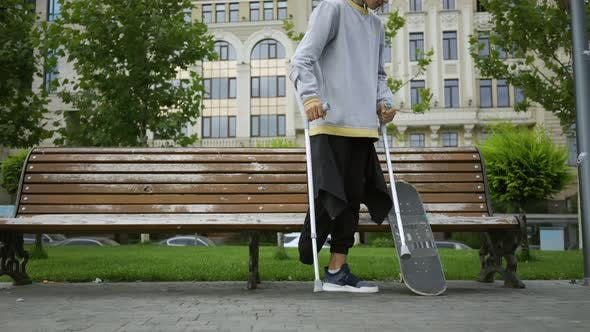 Cover Image for Attractive Man Sits on the Bench in the Park Putting His Crutches and Skateboard Nearby. Active Life