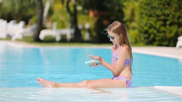 Little Girl with Sunscreen in the Swimming Pool