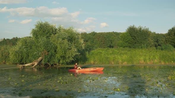 Thumbnail for Fitness woman is floating in kayak at sunset. Brunette female sails in canoe along river in canoe