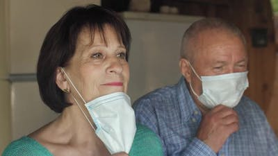 Old Couple Behind Window Take Off Masks
