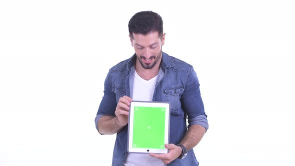 Thumbnail for Happy Young Bearded Hipster Man Showing Digital Tablet and Looking Surprised
