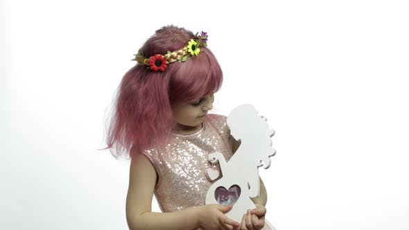 Thumbnail for Girl hält Holz-Bilderrahmen in Form von schwangeren Frauen. Muttertag