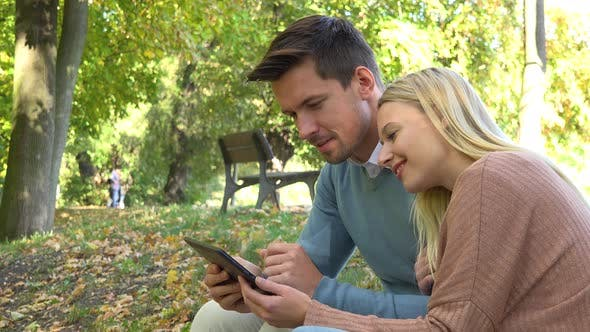 Thumbnail for A Young Attractive Couple Works on a Tablet and Talk in a Park on a Sunny Day - Closeup