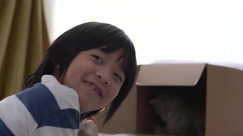Nettes asiatisches Kind, das Snack-Katzen