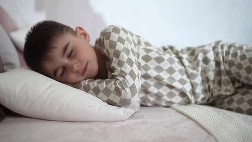 A Little Boy in Pajamas Sleeps on the Bed