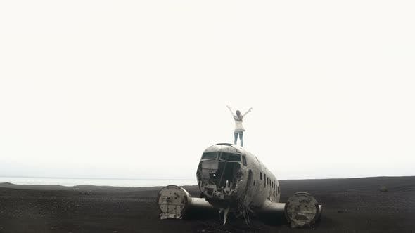 Thumbnail for Freedom Back View of Young Woman in Lopapeysa Standing on the Top of Breaker DC-3 BMC Plane on