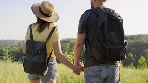 Happy Middle Age Couple Holding Hands Man and Woman with Backpacks Back View