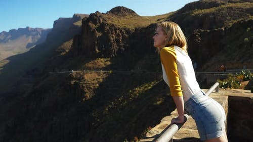 Blonde Model Leaning Over Gran Canaria View Point Railing