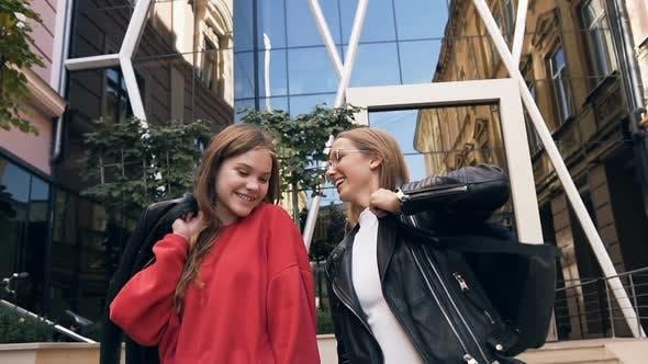 Thumbnail for Two Cheerful Stylish Caucasian Girlfriends Walking Along Street Near Modern Building