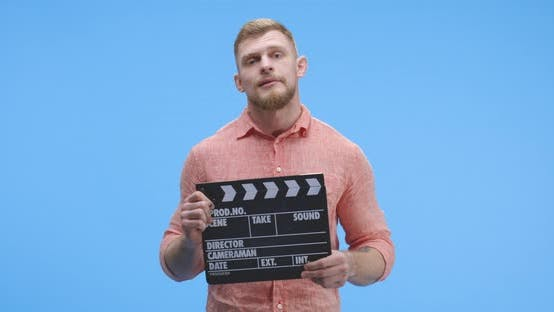 Thumbnail for Bored Man Holding Clapperboard