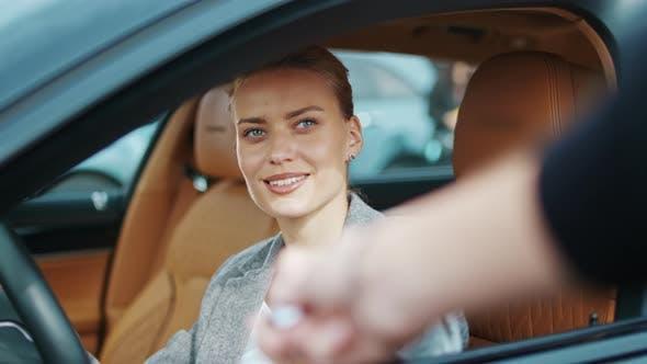 Closeup Woman Receiving Car Keys To New Vehicle. Businesswoman Sitting in Car