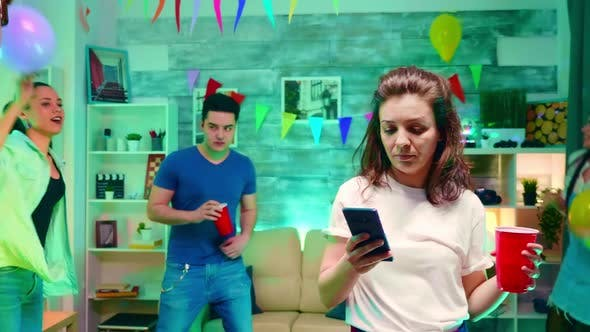 Thumbnail for Bored Girl Texting on Her Smartphone at His Friends Party