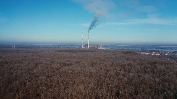 Landscape with smoked polluted atmosphere. Aerial view of high chimney pipes with grey smoke