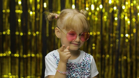 Thumbnail for Child Smiling, Pointing Fingers at Camera. Girl Posing on Background with Foil Golden Curtain