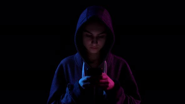 Thumbnail for A Young Woman in a Hood with a Phone in Her Hands. Hacker Makes a Hack Through the Phone. Blue and