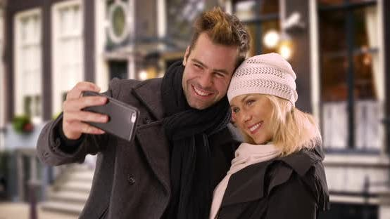 Thumbnail for Happy yuccie couple taking selfies outdoors during winter time