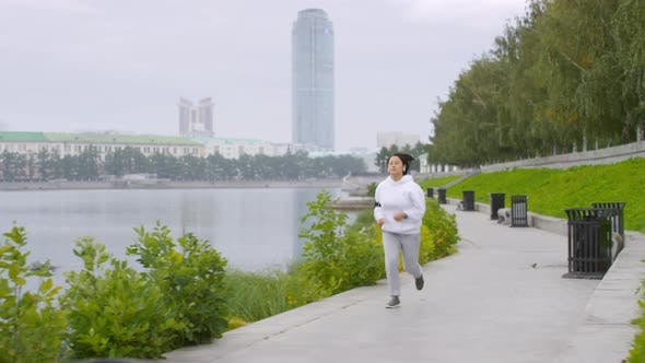 Thumbnail for Asian Woman Listening to Music on Phone and Jogging Along Riverside