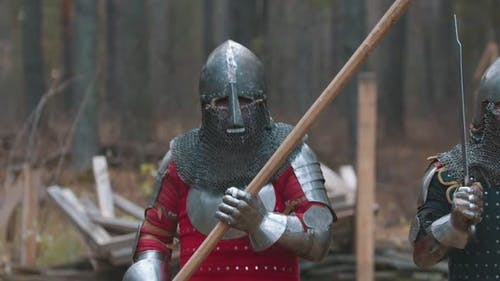 A Man Knight Walking in the Forest in Full Armour Holding a Weapon