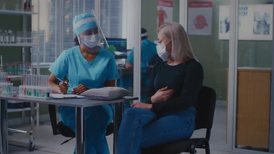 Diverse Female Doctor and Patient Talking During Appointment