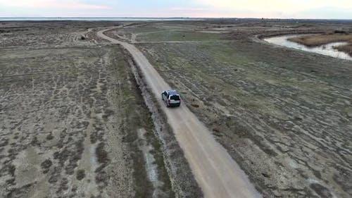 Car Going on Dirt Road on Flat Terrain