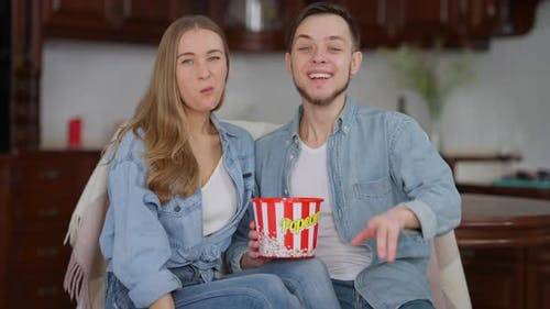 Cheerful Laughing Couple Watching TV Eating Popcorn at Home Indoors