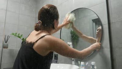 Woman cleaning mirror at home