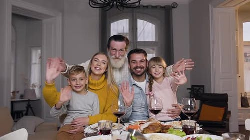 People-Relatives Sitting at the Festive Table and Looking at Camera with Waving Hands