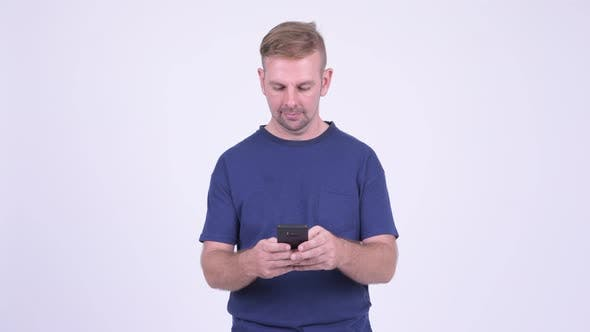 Thumbnail for Portrait of Happy Blonde Man Using Phone