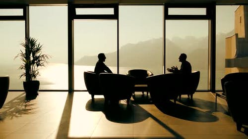 Two Business People Meeting Inside Modern Lobby