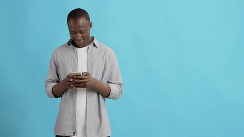 Millennial African American Guy Networking on Cellphone