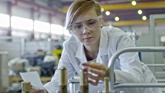 Thumbnail for Young Blonde Female Engineer Inspecting Factory Machine
