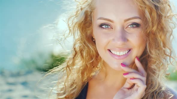 Thumbnail for Close-up of a Beautiful Young Woman Smiling at the Camera. Sunny Day at the Beach Near the Sea