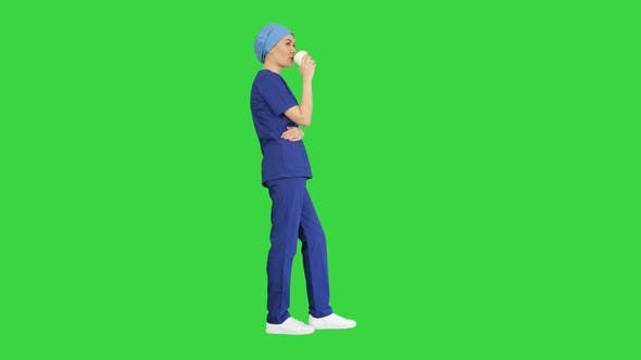 Smiling Female Doctor or Nurse in Blue Uniform Having a Coffee Break on a Green Screen, Chroma Key.