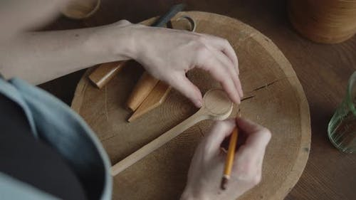 Woman Carpenter Drawing Markup with a Pencil on a Piece of Wood Close-up