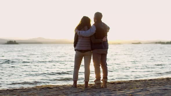 Cover Image for Romantic Couple Embracing and Watching Sunset from Lakeshore