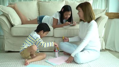 Asian Family Drawing Together In Living Room
