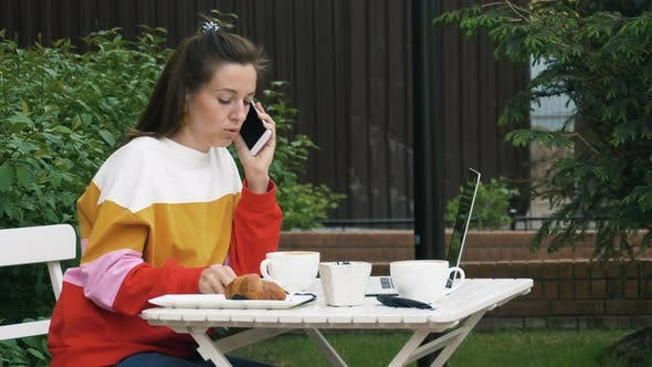 Cover Image for Woman Drinks Coffee and Talking on Mobile Phone