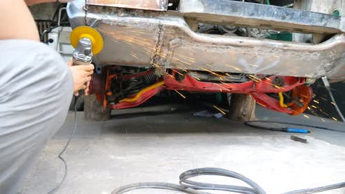 Mechanic Polishing Auto with Electric Tool at Workshop