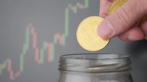 Man Tosses a Bitcoin Into a Piggy Bank