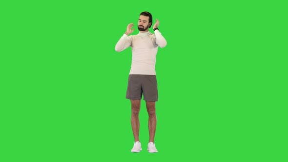Attractive Fit Caucasian Sportsman Doing Warm Up Exercises for Neck on a Green Screen Chroma Key