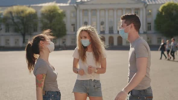 Thumbnail for Social Distancing. Multiracial Friends in Protective Face Mask Greet Their Elbows. Elbow Bump Is New