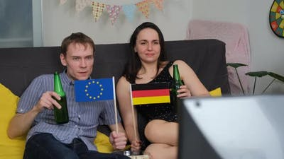 Young Couple Watching Sport Games on TV at Home