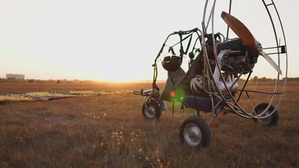 Thumbnail for Motor Paraglider Stands at the Airport in the Rays of Sunset Sunlight. The Camera Moves Along the