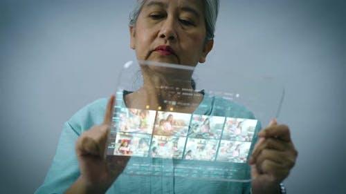 Active Senior Asian Woman Using a Futuristic Tablet