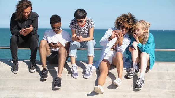 Thumbnail for Young Diverse People with Mobile Phones on Seafront