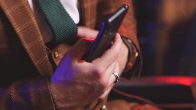 Closeup of Men's Hands with a Smartphone