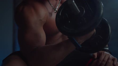 Close Up Shot of Handsome Fitness Man Shirtless Bodybuilder Trains Biceps with Dumbbell in Hands in