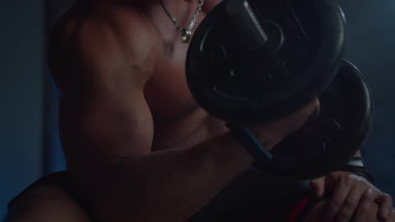 Nahaufnahme des gut aussehenden Fitness-Mannes Hemdloser Bodybuilder trainiert Bizeps mit Hantel in den Händen
