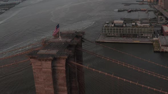 Close Up Circle Flight Over Brooklyn Bridge with American Flag and East River View Manhattan